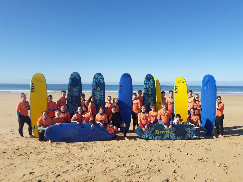 Schüler*innen stehen vor Surfbrettern am Strand