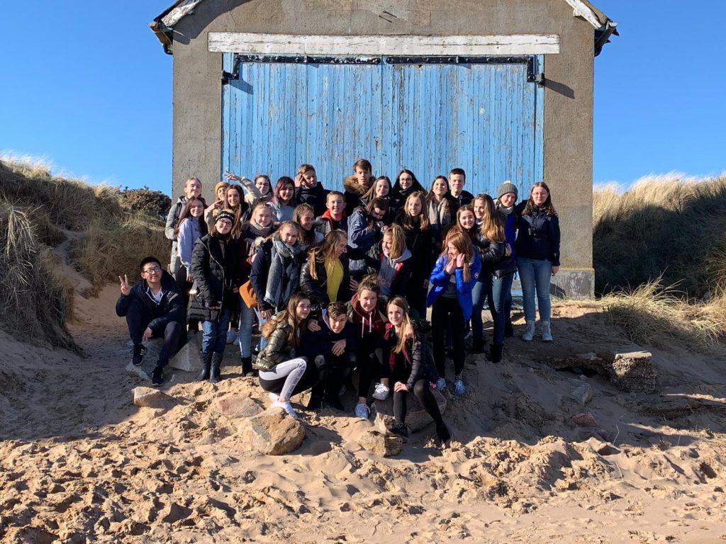 Schüler*innen stehen in Schottland am Strand